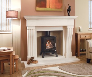 The Silvosa Limestone Fireplace has a solid stone carved shaped and fluted legs together with the curved header and shelf to give a fireplace of impressive proportions. Shown with Bela Vista Stove.